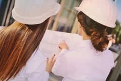 Two young pretty business women industrial engineers in construction helmets with a tablet in hands on a glass building Royalty Free Stock Images