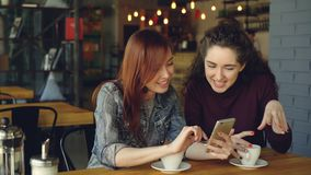 Two young pretty girlfriends are using smartphone in cafe, laughing and talking emotionally. Social media, meeting. Best friends and modern technology concept stock video
