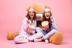 Two young pretty girls dressed in pajamas laughing. While sitting with a big teddy bear and eating popcorn isolated over pink background Stock Image
