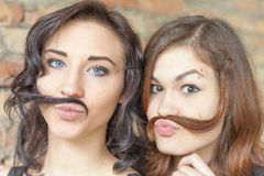 Two young pretty girls making mustache of their hair Stock Image