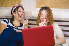 Two young pretty and happy Asian Chinese student girls together at home bedroom using internet social media in laptop computer. Laughing cheerful on bed having royalty free stock photo