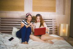 Two young pretty and happy Asian Chinese student girls together at home bedroom watching internet Korean drama with laptop. Computer sitting on bed relaxed royalty free stock photography