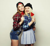 Two young pretty hipster girls. Portrait of two young pretty hipster girls wearing hats and sunglasses holding candys. Studio portrait of two cheerful best Royalty Free Stock Photos