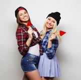 Two young pretty hipster girls. Portrait of two young pretty hipster girls wearing hats and sunglasses holding candys. Studio portrait of two cheerful best stock images