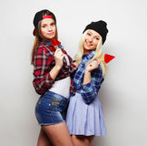 Two young pretty hipster girls. Portrait of two young pretty hipster girls wearing hats and sunglasses holding candys. Studio portrait of two cheerful best stock photography