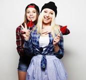 Two young pretty hipster girls. Portrait of two young pretty hipster girls wearing hats and sunglasses holding candys. Studio portrait of two cheerful best Royalty Free Stock Images