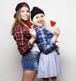 Two young pretty hipster girls. Portrait of two young pretty hipster girls wearing hats and sunglasses holding candys. Studio portrait of two cheerful best stock photos