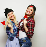 Two young pretty hipster girls. Portrait of two young pretty hipster girls wearing hats and sunglasses holding candys. Studio portrait of two cheerful best Royalty Free Stock Photo