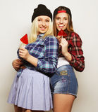 Two young pretty hipster girls. Portrait of two young pretty hipster girls wearing hats and sunglasses holding candys. Studio portrait of two cheerful best Royalty Free Stock Photography