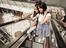 Two young pretty slim girls,wearing casual style,stand next to each other at the escalator in a new mall. stock image
