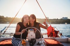 Two young pretty smiling girls, friends driving luxury yacht in sea, showing thumbs up, summer sunset stock photos