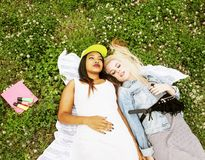 Two young pretty teenager girls best friends laying on grass mak Stock Images