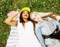 Two young pretty teenager girls best friends laying on grass mak Royalty Free Stock Photos
