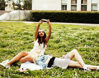 Two young pretty teenager girls best friends laying on grass making selfie photo having fun, lifestyle happy people Royalty Free Stock Photography