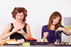 Two young pretty woman housewife cooking with curlers on hair Royalty Free Stock Images