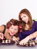 Two young pretty woman housewife cooking with curlers on hair Stock Images
