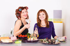 Two young pretty woman housewife cooking with curlers on hair Royalty Free Stock Image