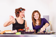 Two young pretty woman housewife cooking with curlers on hair Royalty Free Stock Photo