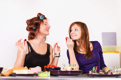 Two young pretty woman housewife cooking with curlers hair Stock Photos