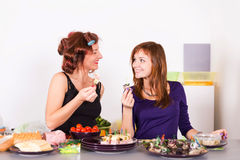 Two young pretty woman housewife cooking with curlers hair Stock Photo