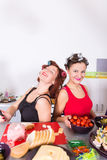 Two young pretty woman housewife cooking with curlers hair Royalty Free Stock Photos