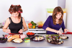 Two young pretty woman housewife cooking with curlers hair Stock Images