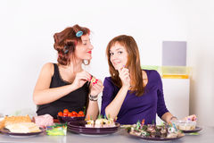 Two young pretty woman housewife cooking with curlers hair Royalty Free Stock Photography