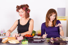 Two young pretty woman housewife cooking with curlers Stock Images