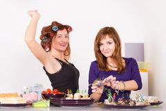 Two young pretty woman housewife cooking with curlers Royalty Free Stock Photos