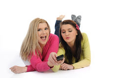 Two young pretty woman watching tv. Two young pretty woman watching television and switching channels on remote control Royalty Free Stock Photography
