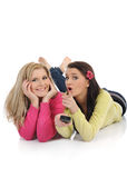 Two young pretty woman watching tv. Expressions.two young pretty woman friends watching television and switching channels on remote control Royalty Free Stock Photography