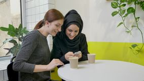 Two young pretty womans sitting in cafe, one of them muslim woman in hijab taking selfie with phone and looking in phone.  stock video footage