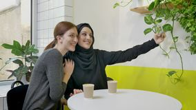 Two young pretty womans sitting in cafe, one of them muslim woman in hijab taking selfie with phone and posing, smiling.  stock video