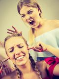 Two women having argue fight. Two young pretty women being mad at each other having argue fight pulling hair. Friendship rivaly and envy problems Stock Photos