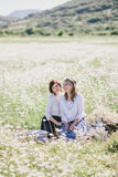 Two young pretty women having picnic with tea in chamomile field Stock Photography
