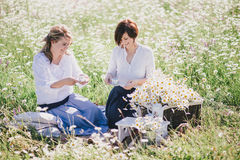 Two young pretty women having picnic with tea in chamomile field Stock Photo
