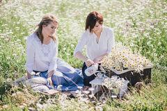 Two young pretty women having picnic with tea in chamomile field Royalty Free Stock Photos