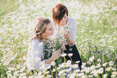 Two young pretty women posing in a chamomile field. Female friendship Stock Photo