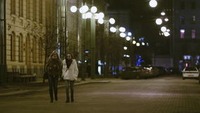 Two young pretty women are walking and talking on the night street of the city. Two young pretty women, blonde and brunette, are walking and talking on the night stock footage