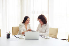 Two young pretty women working together with gadgets in the offi Stock Image