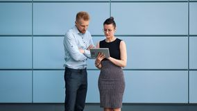Two young professional business people greeting shaking hands working as team using tablet. Medium long shot. Businesswoman and busy businessman having stock footage