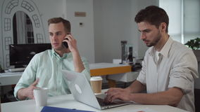 Two young professional businessmen are working in a light and modern open plan office. stock video