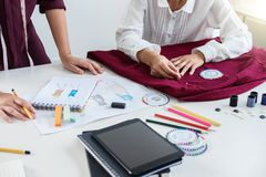 Two young professional Fashion designer colleagues working and p stock photos