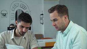 Two young professional men working together at the modern office stock video footage