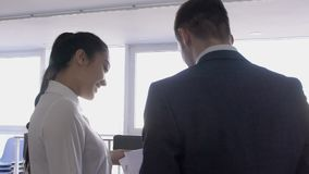Two young professionals are discussing ideas for business promotion in large company, man and woman standing, talking. Smiling cheerfully in good mood stock video footage