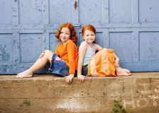Two young redhead girls. Posing back to back by a garage door Royalty Free Stock Images
