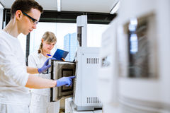 Two young researchers carrying out experiments in a lab Stock Image