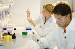 Two young researchers at work. Wearing white clothing Royalty Free Stock Photos