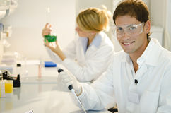 Two young researchers at work. Wearing white clothing Royalty Free Stock Photography