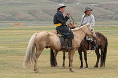 Two young riders. KHARKHORIN, MONGOLIA, July 8, 2013 : Two riders wait in the steppe before Naadam festival. Half of mongolian population has a nomadic life Royalty Free Stock Images